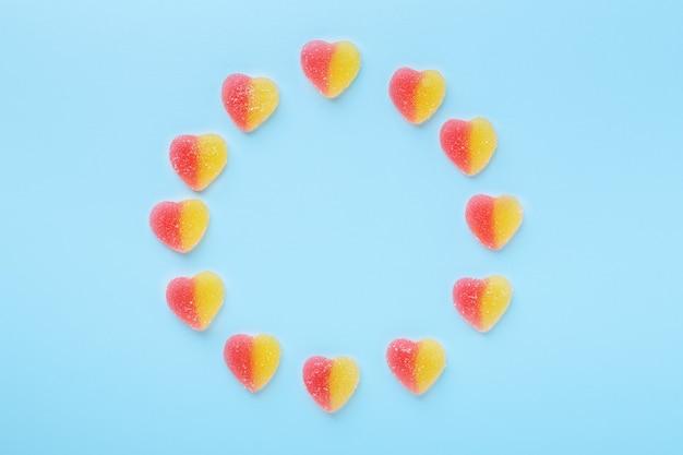 Bunte gummiartige herzen auf blauem tisch. geleesüßigkeiten in kreisform.