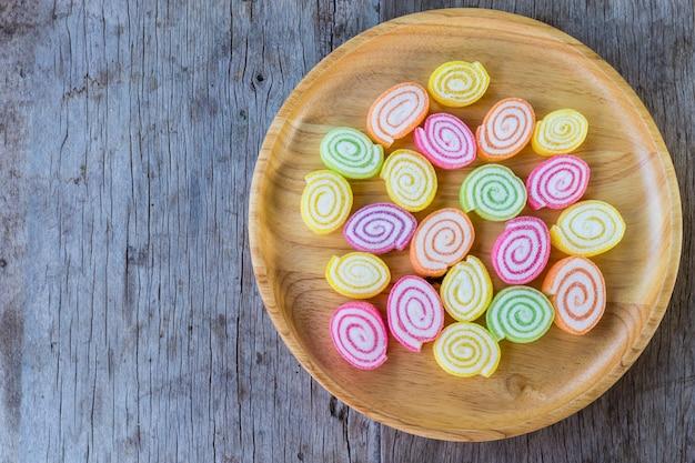 Bunte gummiartige süßigkeit auf hölzernem teller und auf holztisch.