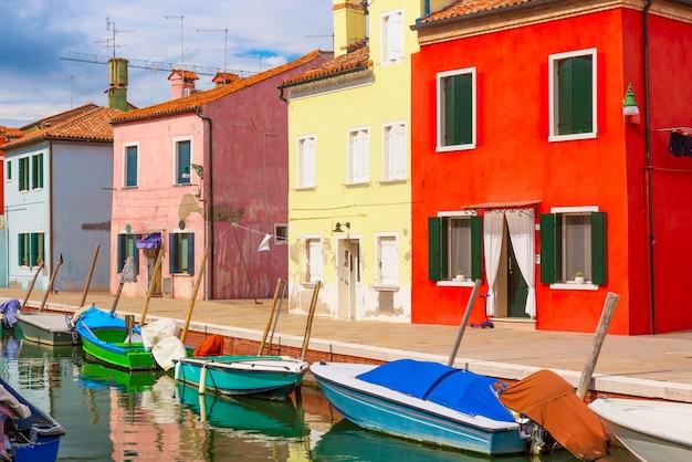Bunte häuser und boote in burano-insel mit bewölktem blauem himmel nahe venedig, italien,