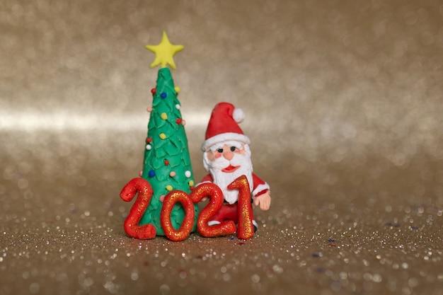Bunte handgemachte miniatur von weihnachtsbaum und weihnachtsmann mit jahr 2021