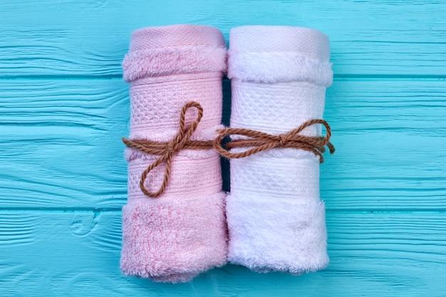 Bunte handtücher auf blauem hintergrund aus holz aufgerollt. draufsicht flach.