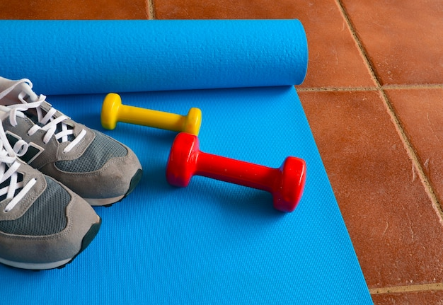 Bunte hanteln, turnschuhe und blaue yogamatte