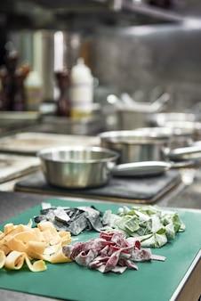 Bunte hausgemachte pasta auf dem schneidebrett in der küche liegend und bereit zum kochen