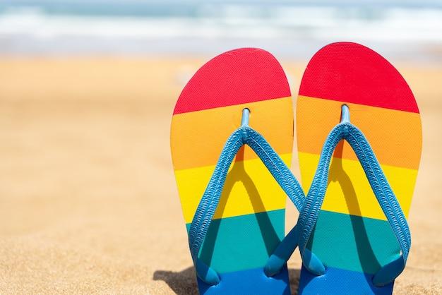 Bunte hausschuhe am strand an einem sommertag flip-flops mit gay-pride-flagge