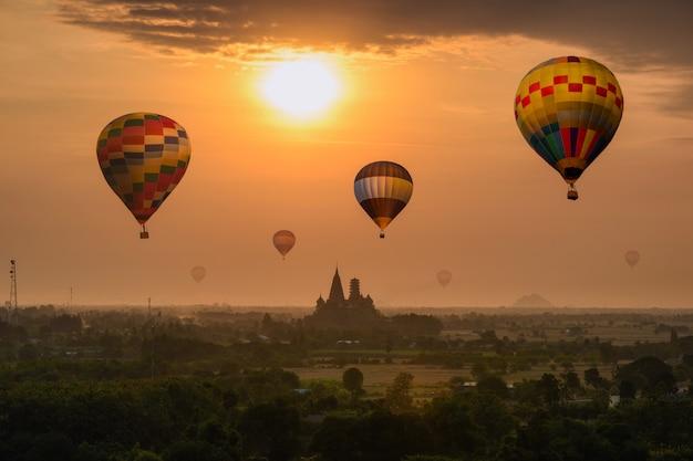 Bunte heißluftballone, die auf wat tham sua-tempelgebäude auf hügel am sonnenaufgangmorgen fliegen