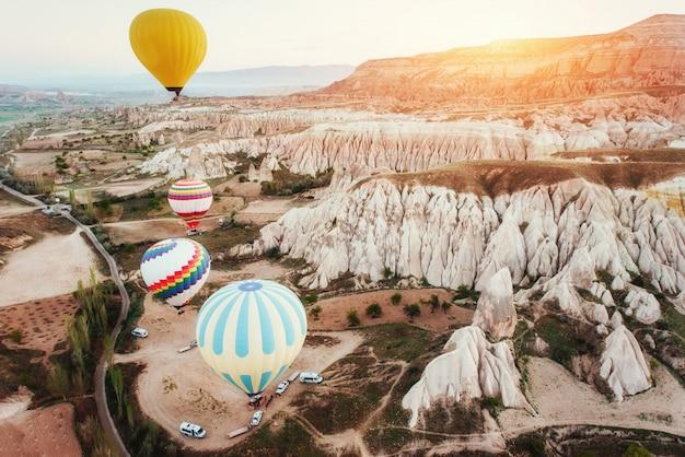 Bunte heißluftballons, die über rotes tal bei kappadokien fliegen,