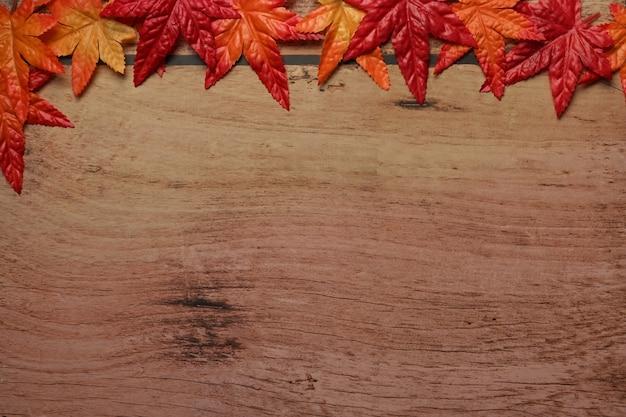 Bunte herbstahornblätter auf hölzernem hintergrund mit kopienraum.