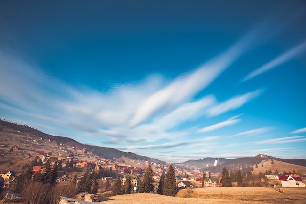 Bunte herbstlandschaft im bergdorf. dramatischer und malerischer blauer himmel. bukovel, karpaten, ukraine, europa. schönheitswelt erkunden