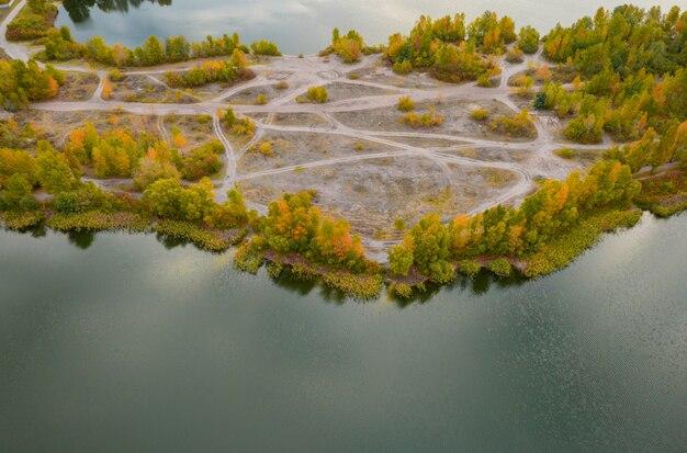 Bunte herbstlandschaft mit fluss und schönen fallbäumen luftbild drohnenschuss