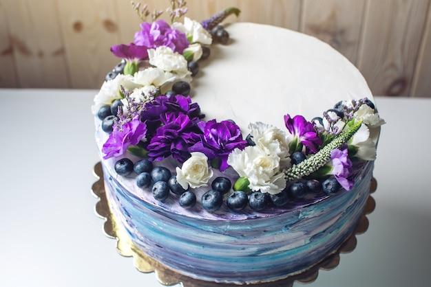 Bunte hochzeitstorte mit schönen lila blumen und blaubeeren