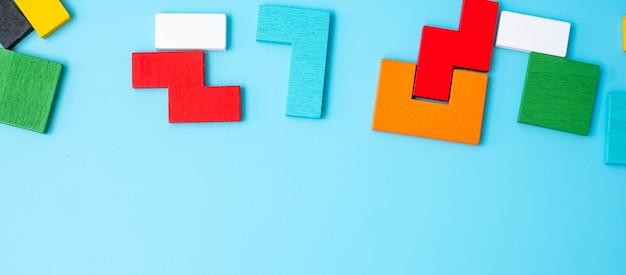 Bunte hölzerne puzzleteile auf blauem hintergrund, geometrischer formblock mit kopienraum. konzepte des logischen denkens, rätsel, lösungen, rationalität, strategie, welttag der logik und bildung