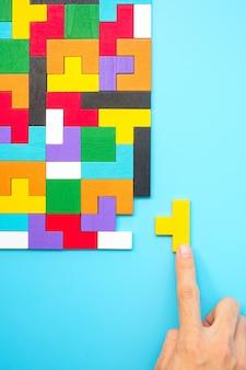Bunte holzpuzzleteile auf blauem hintergrund, geometrischer formblock. konzepte des logischen denkens, rätsel, lösungen, rationalität, strategie, welttag der logik und bildung
