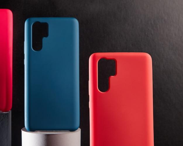 Bunte hüllen für moderne smartphones stehen auf ständern auf dem tisch ein objekt im fokus unscharfer hintergrund