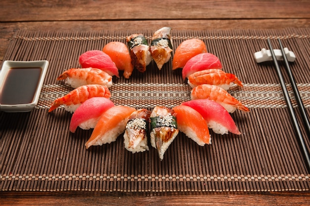 Bunte japanische sushi-set, meeresfrüchte. große auswahl an nigiri nigiri serviert wie kreis auf brauner strohmatte, nahaufnahme. nationale meeresfrüchte, restaurantmenüfoto.