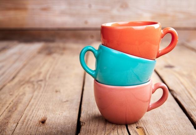 Bunte kaffeetassen auf holztisch über schmutzhintergrund