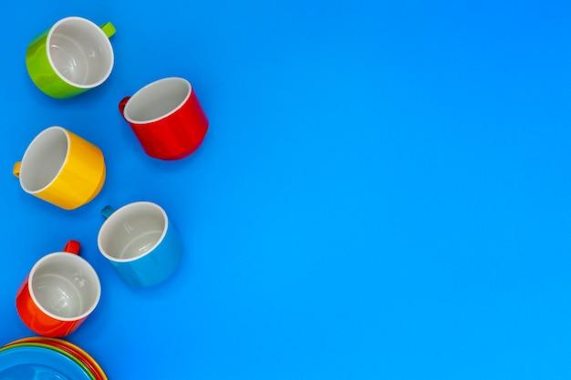 Bunte kaffeetassen lokalisiert auf blauem hintergrund