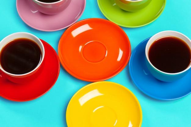 Bunte kaffeetassen und untertassen auf buntem vibrierendem
