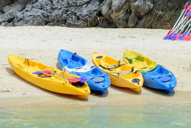 Bunte kajaks auf weißem sand setzen am sonnigen tag, thailand auf den strand