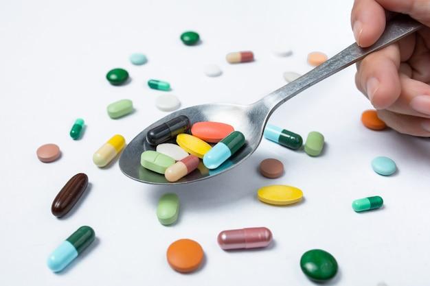 Bunte kapseln und pillen auf löffel. gesundheit