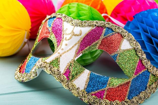 Bunte karnevalsmaske und peper balls auf blauer oberfläche. grußkartenkonzept für geburtstag, karneval, party, einladung