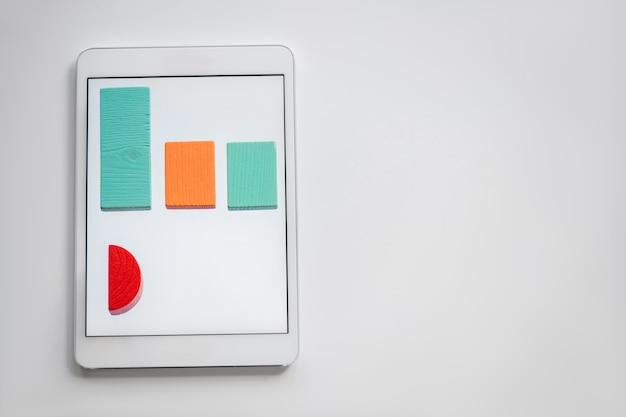 Bunte karte aus flachen holzsteinen, die in reihe auf dem bildschirm des digitalen tabletts mit copyspace auf der rechten seite liegen