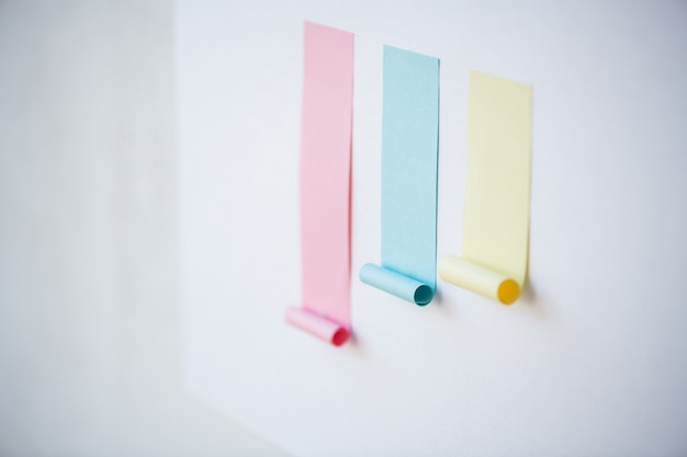 Bunte karte bestehend aus leeren rosa und kleineren blauen und gelben klebrigen papieren, die auf whiteboard oder wand geklebt werden