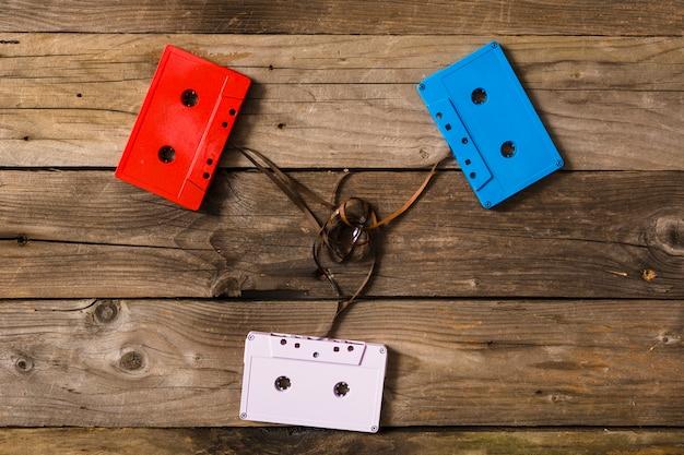 Bunte kassetten mit verwirrtem band auf hölzernem hintergrund