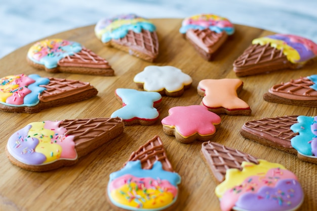 Bunte kekse auf holzbrett. kekse mit zuckerguss. leckereien aus dem café. knusprig glasierte süßigkeiten.