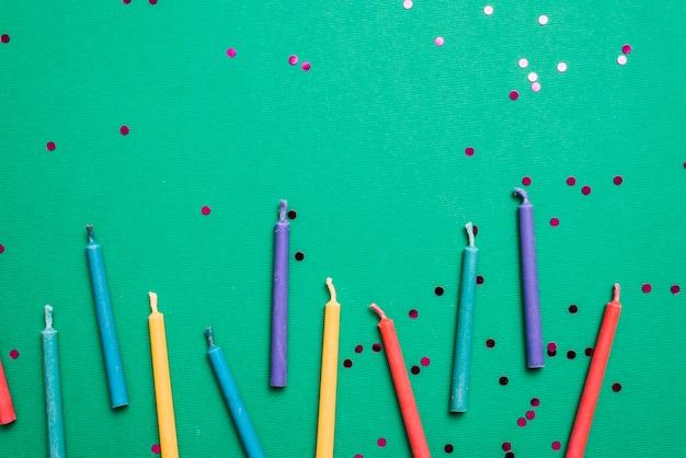 Bunte kerzen mit konfetti auf grünem hintergrund