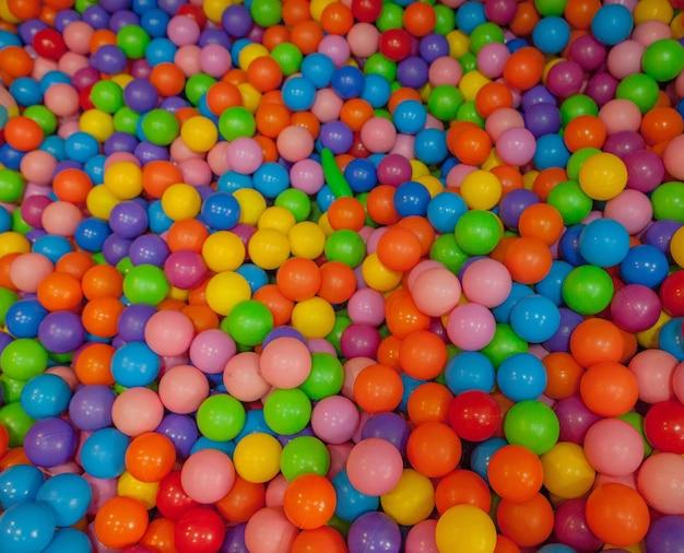 Bunte kinderbälle. mehrfarbige plastikkugeln. achildrens spielzimmer. hintergrundbeschaffenheit von mehrfarbigen plastikbällen auf spielplatz.