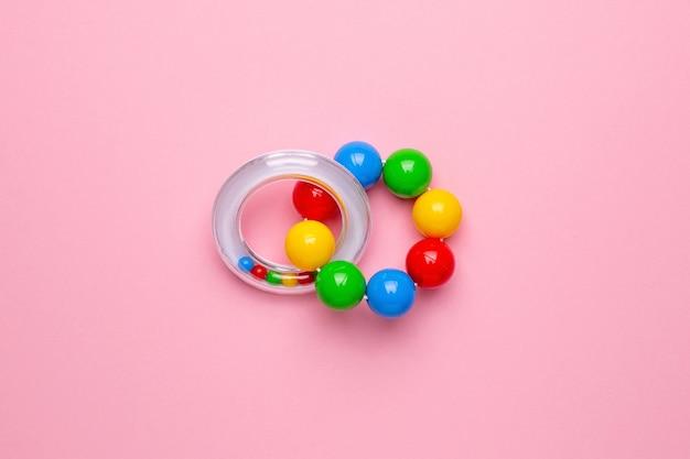 Bunte kinderrassel auf einem rosa hintergrund, spielzeug für kleinkinder und babys draufsicht