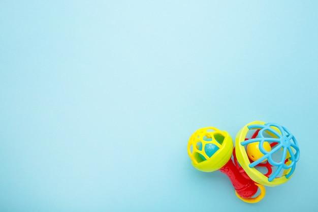 Bunte kinderrasseln auf einem blau. babykonzept