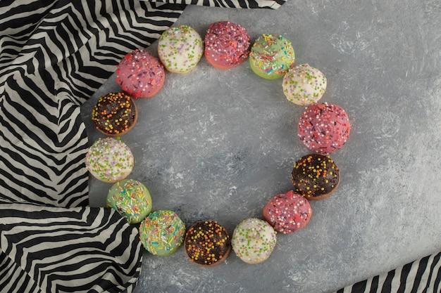 Bunte kleine donuts der süßen schokolade mit streuseln.