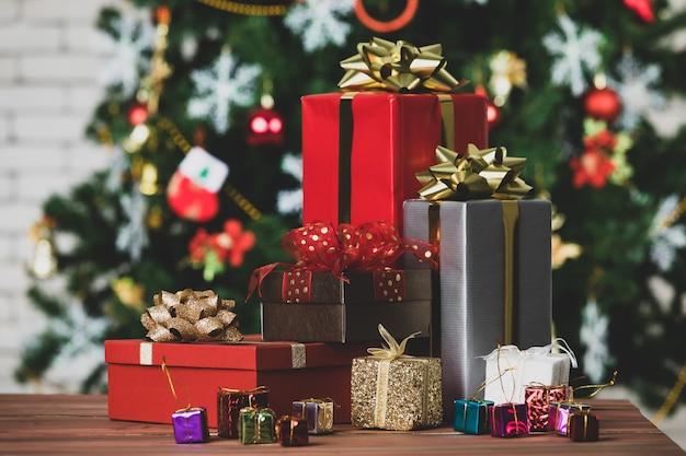 Bunte kleine und große geschenkboxen mit glänzender bandfliege an der ecke des holztisches vor dem voll dekorativen schönen heiligabend-kiefer und der backsteinmauer in unscharfem hintergrund.