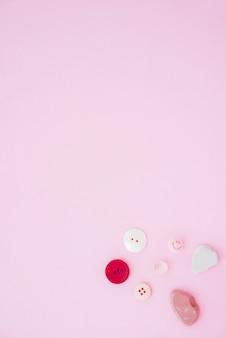 Bunte knöpfe und seife auf der ecke des rosa hintergrundes