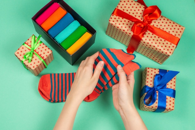 Bunte kollektion von baumwollsocken als geschenk in frauenhänden. geschenk.