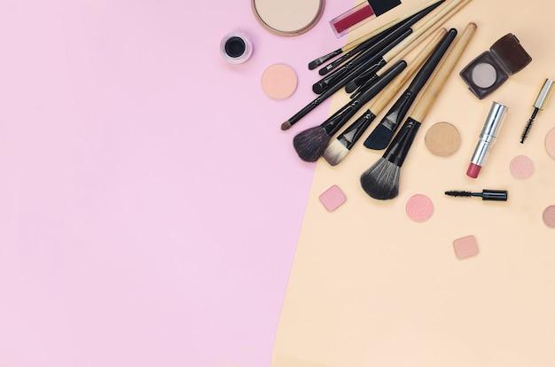 Bunte kosmetik, die auf rosa und gelber oberfläche liegt