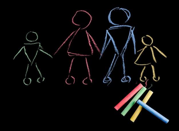 Bunte kreiden und kinderbild der glücklichen familie gemacht mit kreide lokalisiert auf schwarzem hintergrund