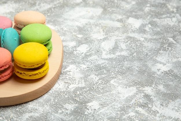 Bunte kuchen der französischen macarons der vorderansicht auf den süßen keksen des weißen oberflächenkuchen-tortenzuckerkekses