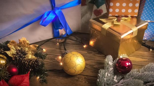 Bunte kugeln, girlanden und weihnachtsgeschenke auf holzschreibtisch