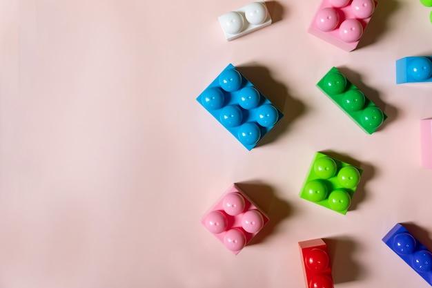 Bunte kunststoffbausteine auf rosa hintergrund, platz für text kopieren