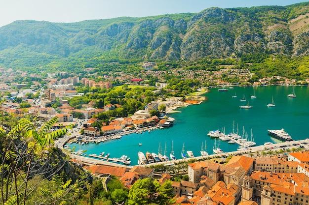 Bunte landschaft mit booten und yachten in marina bay, meer, bergen, blauem himmel. draufsicht der bucht von kotor, montenegro