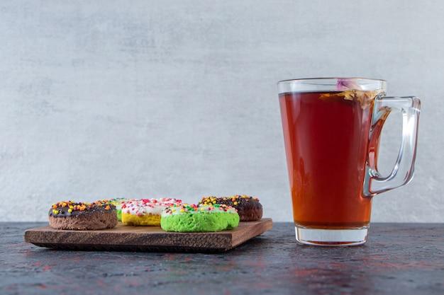 Bunte leckere donuts auf holzbrett mit glas tee.