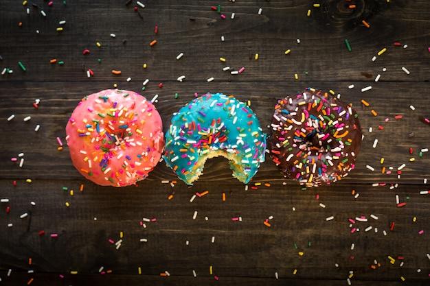 Bunte leckere funkelnde donuts auf einer holzoberfläche