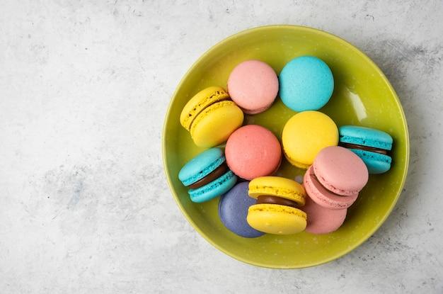Bunte leckere macarons auf grünem teller und auf weißem tisch.