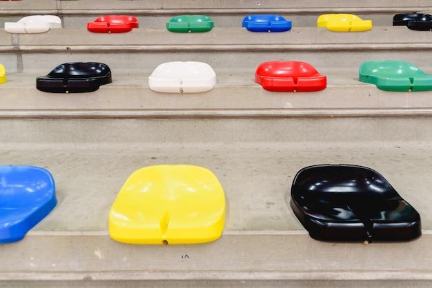Bunte leere plastiksitze in den ständen eines sportstadions.