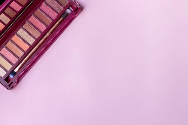 Bunte lidschattenpalette in den rosa farben auf einem rosa, lila papierhintergrund mit kopienraum. professionelle farbpalette für augen make-up mit matten und schimmernden schatten