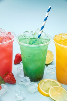 Bunte limonaden mit früchten in plastikbechern