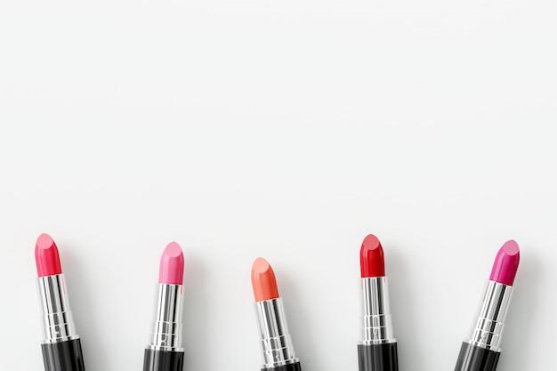 Bunte lippenstifte auf weißem hintergrund. schönheitskonzept
