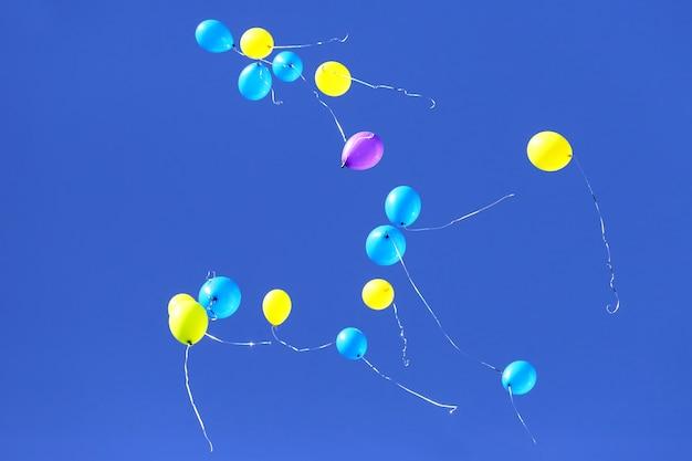 Bunte luftballons fliegen in den blauen himmel